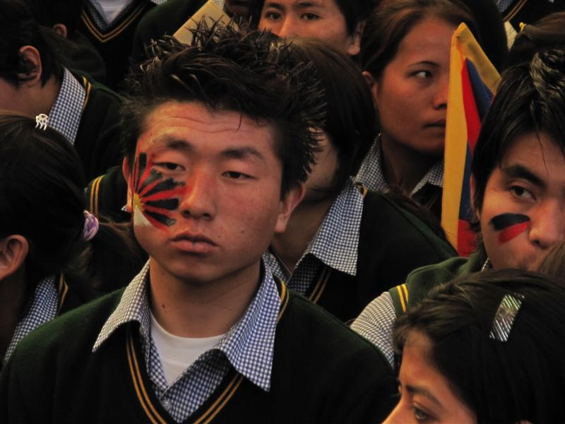 Young Tibetan boy sketches his face with Tibetan Flag.