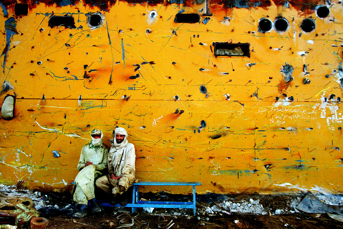 Two workers take a short break while welding inside a ship's hull