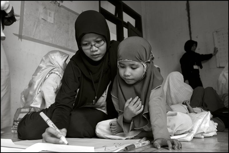 A student of the Fajar Hidayah organization helps a young girl with writing some English at an orphanage in Banda Aceh Indonesia