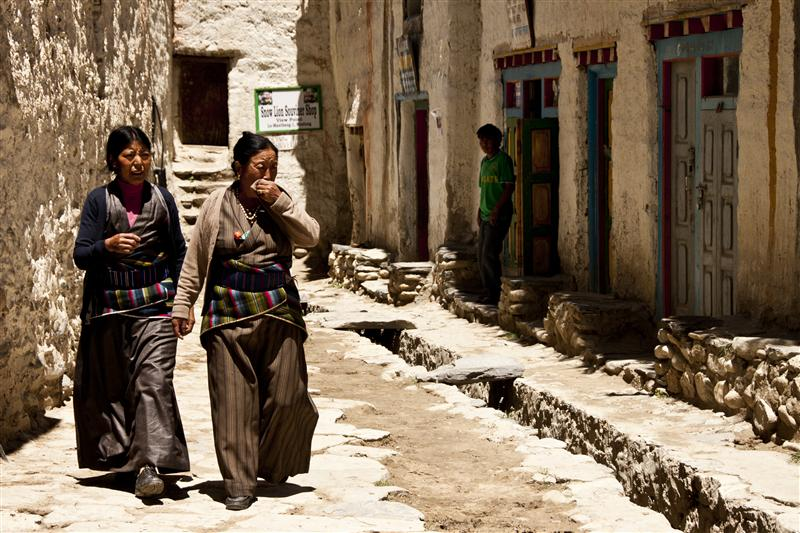 Traditionally dressed women walk pass inside the walled city of Lo Manthang, Upper Mustang