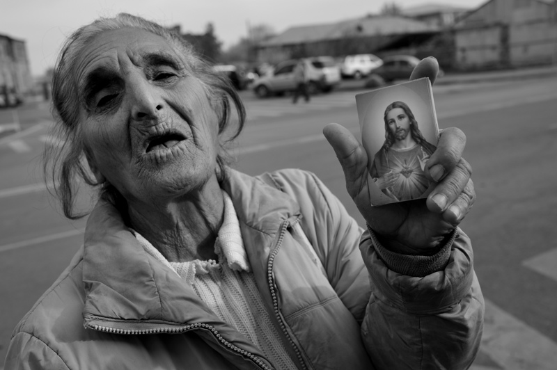 Woman sells a postcard of the Christ outside the Mother See of Holy Etchmiadzin, the world's oldest national church