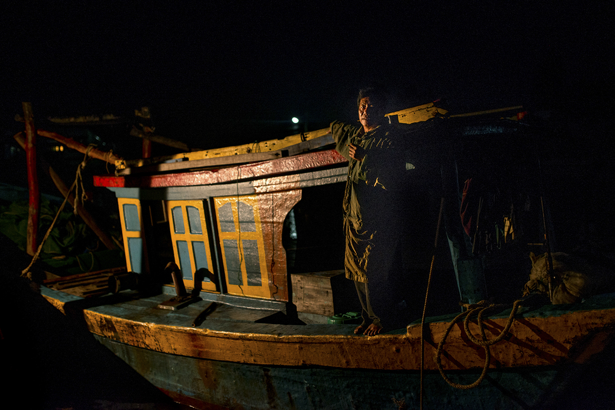 A shrimp fisherman stands on the gunnels of his vessel