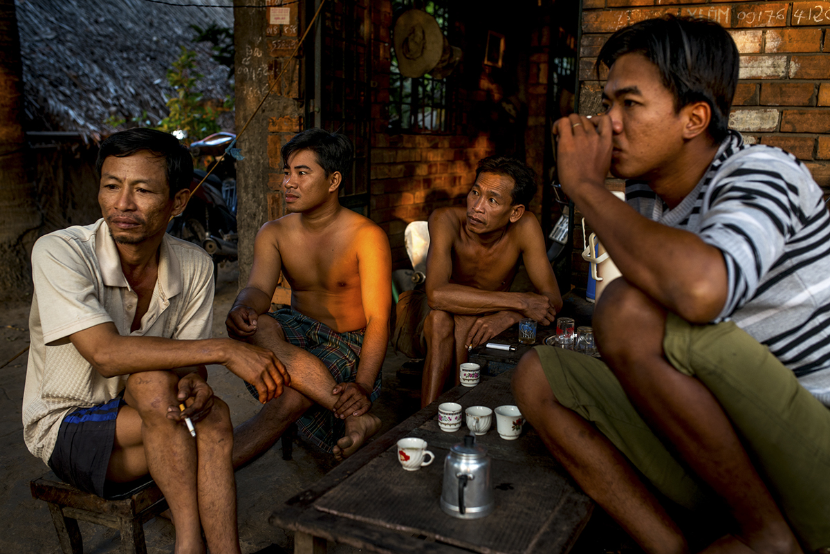 Shipyard workers drink tea before the day's work begins