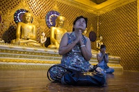 A woman prays in the pagoda of Shwedagon