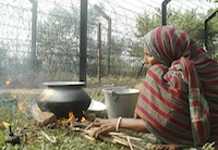 Woman prepares food infront of international border fencing at Lankamura village of South Tripura