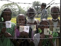Indians standing outside of the International Barbed Wire Border Fence
