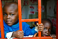 Children peek through a window at their class