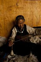 An old Loba women makes wool inside an old house with traditional Tibetan architecture.