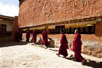 Buddhist monks do the kora, a religious walk alongside the monastery in Tsarang, Upper Mustang