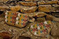 Sacred Tibetan religious text scripted in stones, a common Tibetan Buddhism practice.