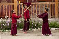 Young monks play with wooden sticks inside the monastery complex in Lo Manthang.