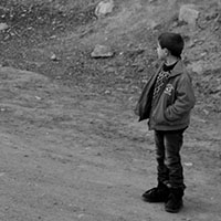 Hay truck passes a boy on the roadside north of Agarak