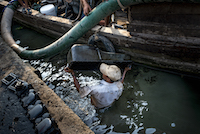 A worker cleans an oilpan in the river