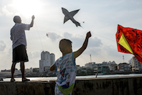 Residents of a fisherman's village fly kites