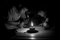 Burmese immigrants Thailand farms labourers writing by candlelight